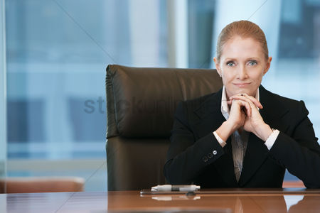 Interior : Businesswoman sitting at conference table portrait