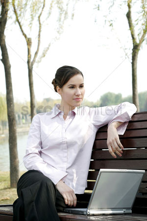 Modern lifestyle : Businesswoman sitting on the bench thinking while using laptop