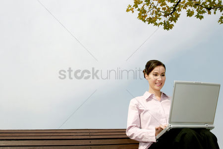 Three quarter length : Businesswoman sitting on the bench using laptop
