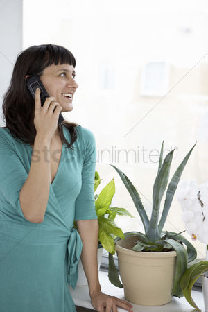 Houseplant : Businesswoman smiling using cell phone by plant and window