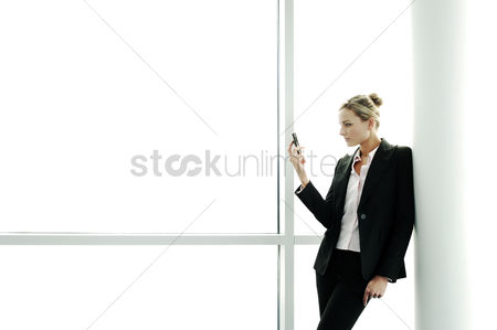 Three quarter length : Businesswoman taking picture with a cell phone