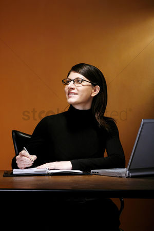 Bespectacled : Businesswoman thinking while writing