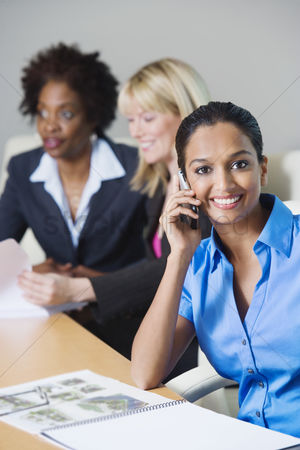 Posed : Businesswoman using cell phone during meeting