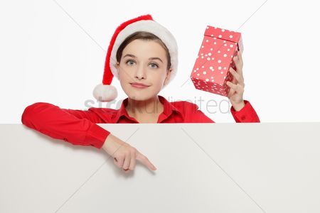 Head shot : Businesswoman with santa hat holding present and pointing at white board