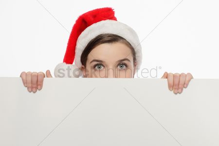 Creativity : Businesswoman with santa hat peeking from behind a white board