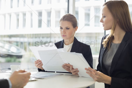 Businesswomen : Businesswomen discussing over documents in office cafeteria