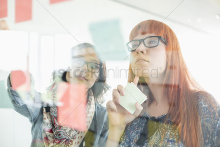 Businesswomen : Businesswomen reading sticky notes on glass wall in creative office