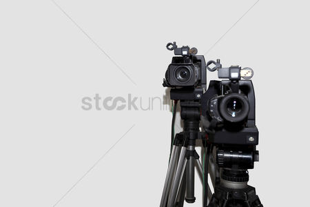 Technology background : Camera and tripod against white background