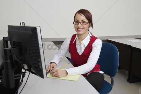 Appearance : Cheerful businesswoman sitting at desk