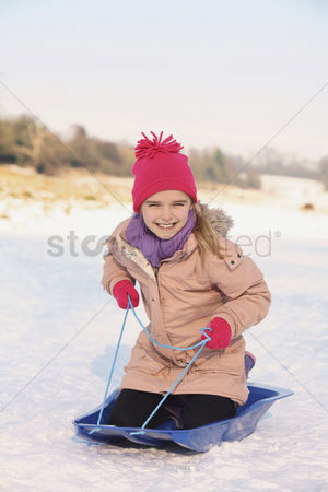 Cold temperature : Cheerful girl riding on sled