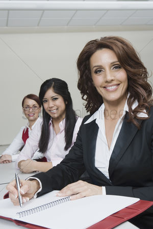 Notepad : Cheerful multi racial businesswomen sitting at desk