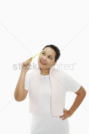 Tooth brush : Cheerful woman holding up a tooth brush  contemplating