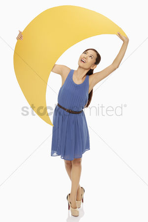 Amazed : Cheerful woman holding up a yellow crescent moon