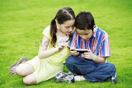 Children playing : Children looking at a handheld game device