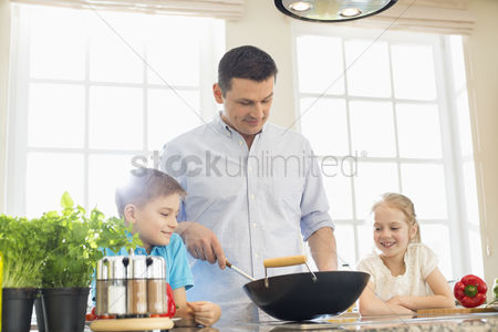 Pre teen : Children looking at father preparing food in kitchen