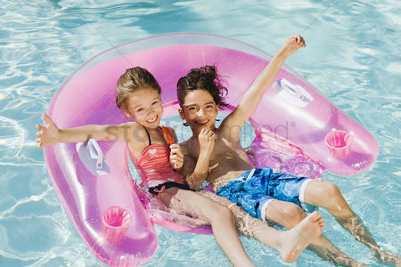 Young boy : Children playing on inflatable toy in swimming pool