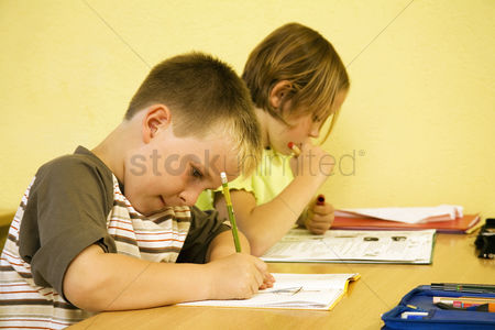 School children : Children writing in the classroom