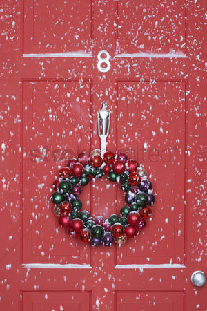 Winter : Christmas wreath hanging on door with snowfall