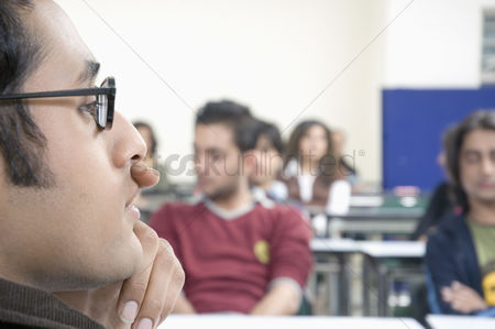 Respect : Close-up of a professor sitting in a lecture hall with his hand on his chin
