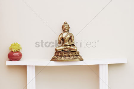 God : Close-up of a statue of buddha and a flower vase