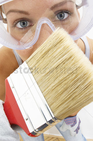 Goggle : Close-up of a woman with goggles using a brush to brush the camera