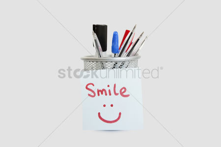 Collection : Close-up of adhesive notepaper with smiley face stuck on pen holder over white background