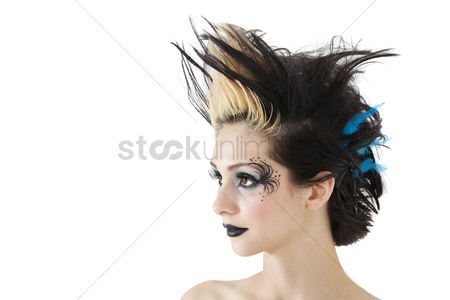 Fashion : Close-up of beautiful gothic woman with spiked hair and face painting over white background