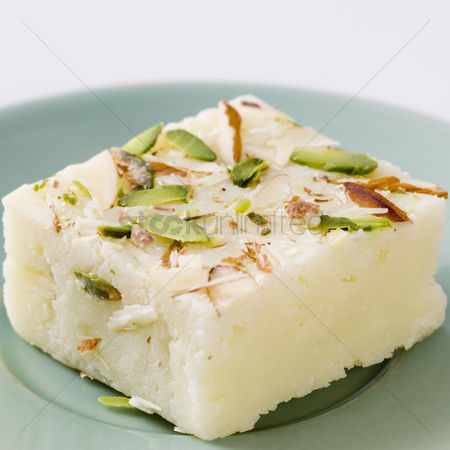 Almond : Close-up of burfi garnished with almond and pistachio
