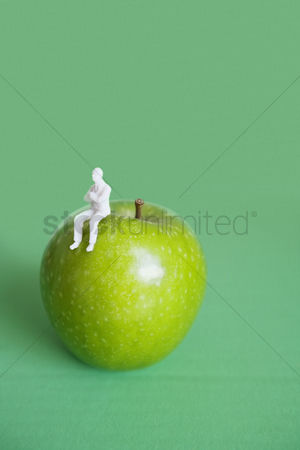Sculpture : Close-up of human figurine sitting on green apple over colored background