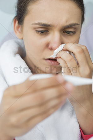 Thermometer : Close-up of worried woman taking her temperature