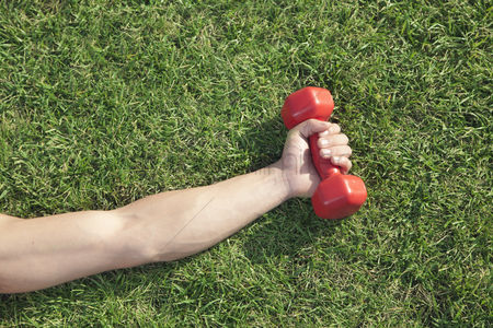 Dumbbell : Close up on hand holding red dumbbell in grass