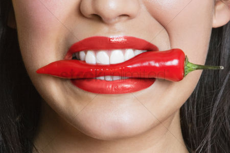 Smiling : Close-up portrait of hispanic woman biting red pepper