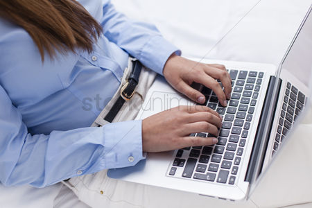 Furniture : Close-up view of hands using laptop