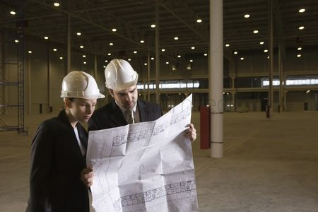 Spacious : Colleagues study blueprint in empty warehouse