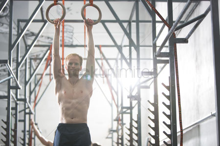 Muscle training : Confident man exercising with gymnastic rings in crossfit gym