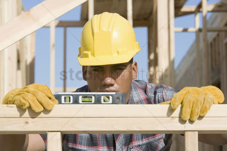 Spirit : Construction worker using spirit level on building
