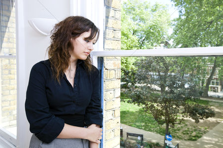 Proud : Contemplative businesswoman looking out the window