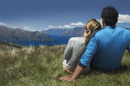 People : Couple cuddling looking over lake and hills back view
