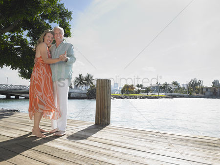 Closeness : Couple embracing standing on pier portrait