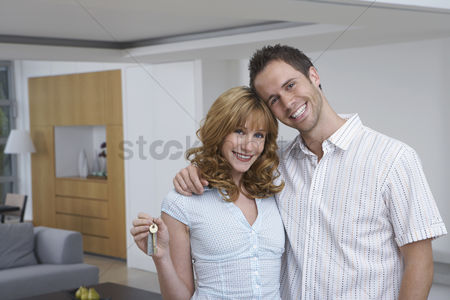 Smiling : Couple embracing woman holding key in new home portrait