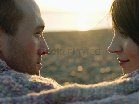 Relationships : Couple face to face wrapped in blanket on beach close up