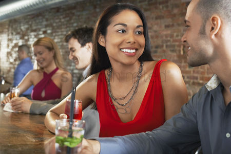 Appearance : Couple holding cocktails sitting at bar