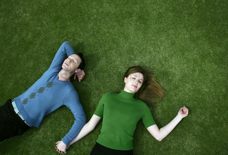Enjoying : Couple holding hands while lying on the field