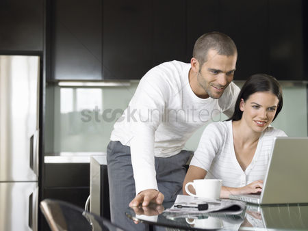 Interior : Couple looking at lap top in modern kitchen