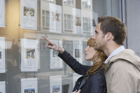 Selection : Couple looking in window outside estate agents