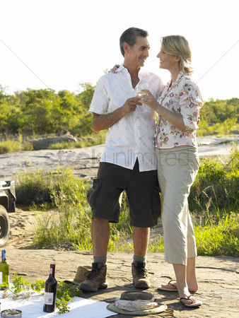 Wine bottle : Couple on picnic toasting looking in eyes smiling