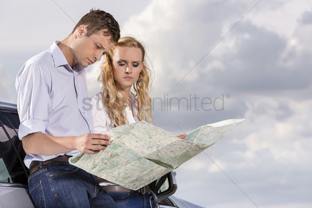 Land : Couple reading map while leaning on car against cloudy sky