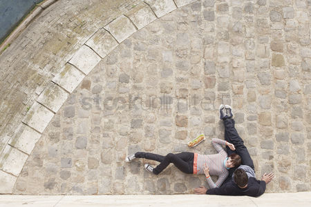 Sitting on lap : Couple relaxing on cobble stones view from above