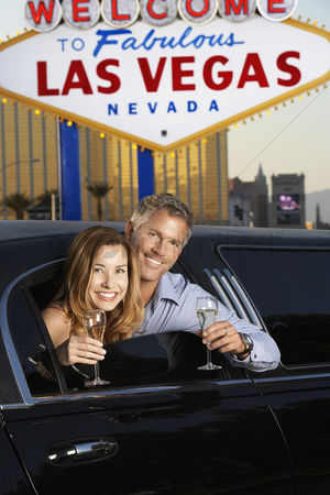 Toasting : Couple sitting in limousine with drinking glasses in front of welcome to las vegas sign