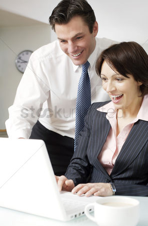 Husband : Couple smiling while using laptop
